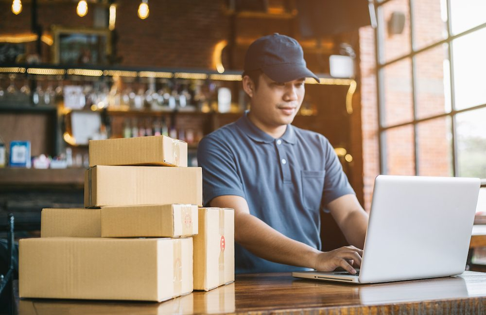 A man prepares orders while leasing a warehouse for his ecommerce business