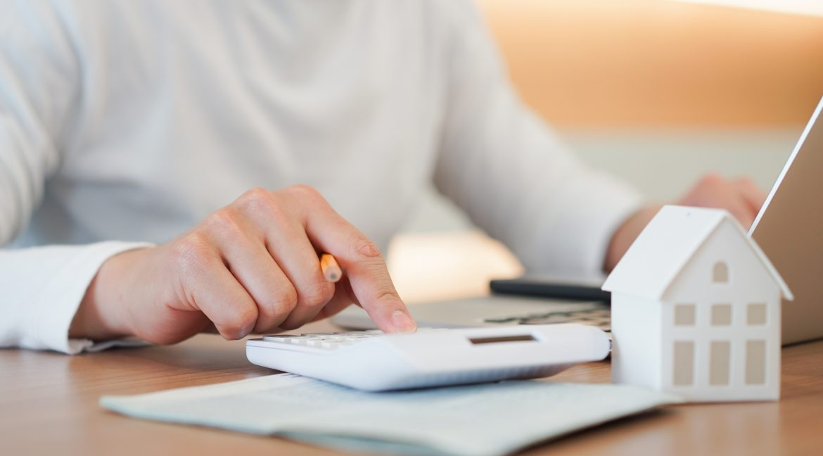 A property management company employee uses a calculator to determine the value of a home.