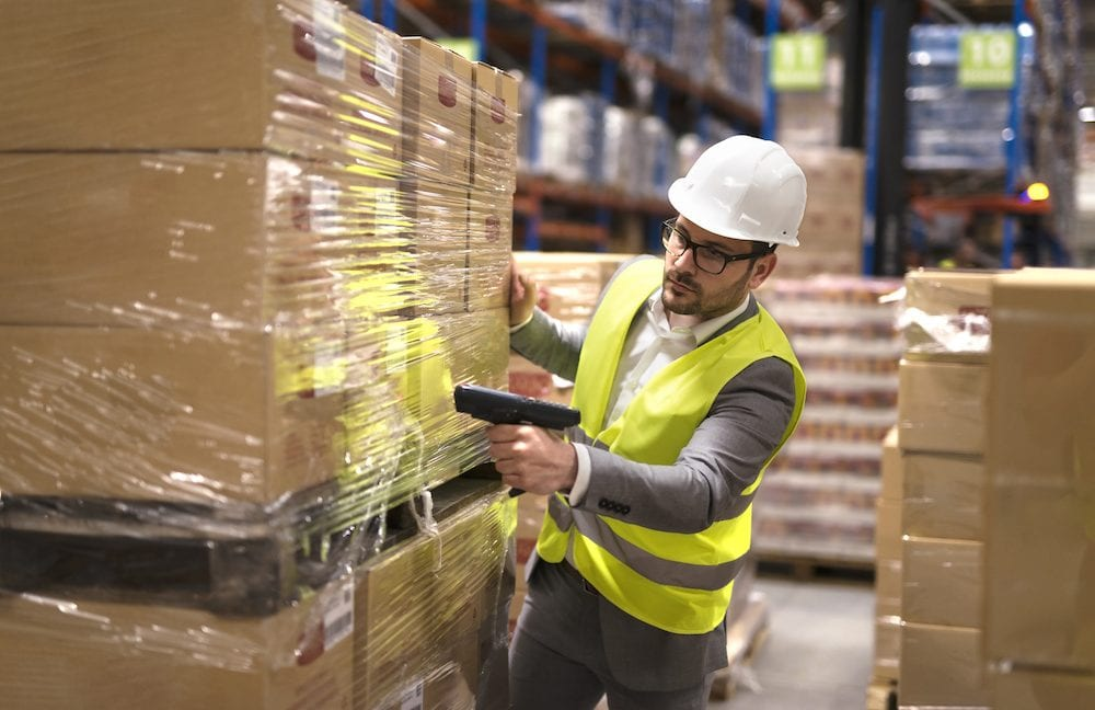 A warehouse employee scans boxes, improving warehouse productivity.