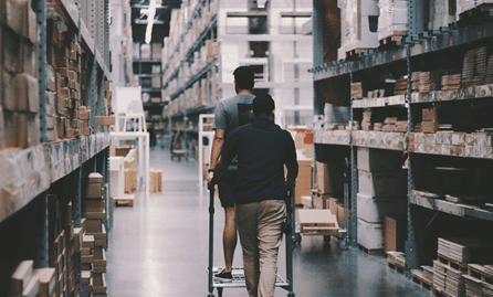 Two men going down a warehouse aisle.