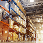 Warehouse aisle with packed boxes and pallets with light shining at the end of the hall