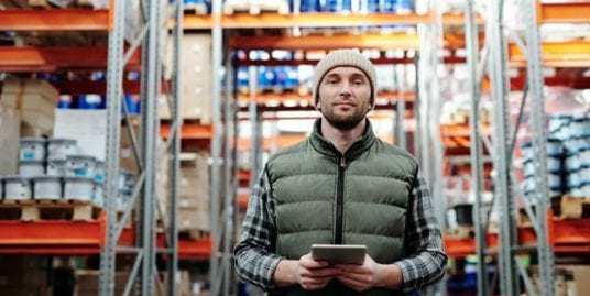 Man in vest holding tablet in aisle of warehouse