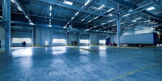Empty warehouse space with garage doors and semi truck