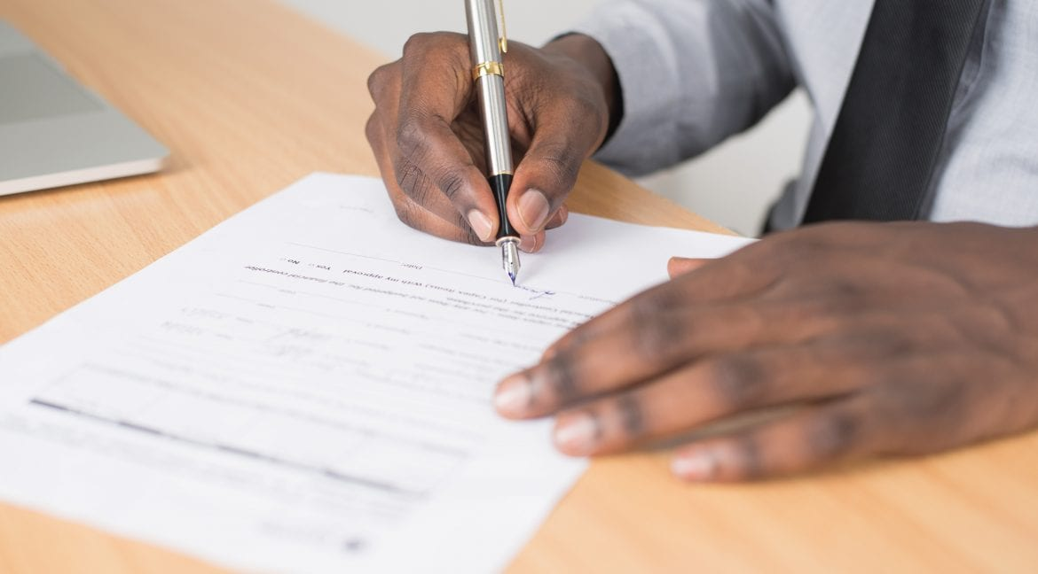 Man in formal clothing signing lease or contract with pen