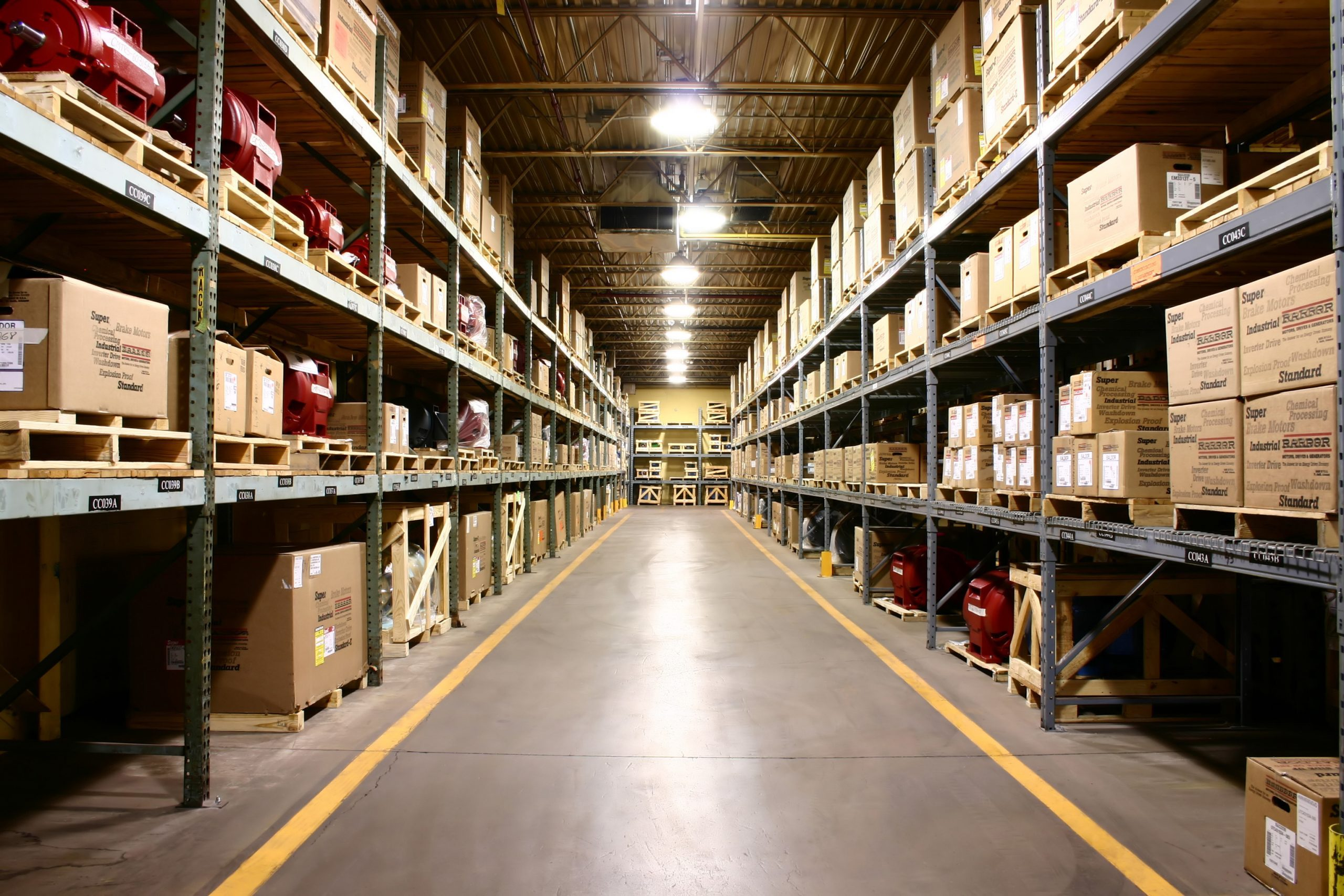 Aisle in warehouse with boxes on shelves.