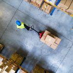 Young male warehouse worker pulling a pallet truck with boxes.