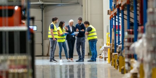 five people working together at the end of a warehouse hallway, some are wearing yellow vests