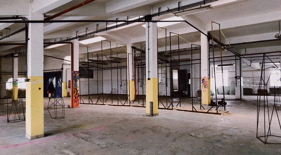 A large, empty warehouse with high ceilings held up by large white and yellow pillars.