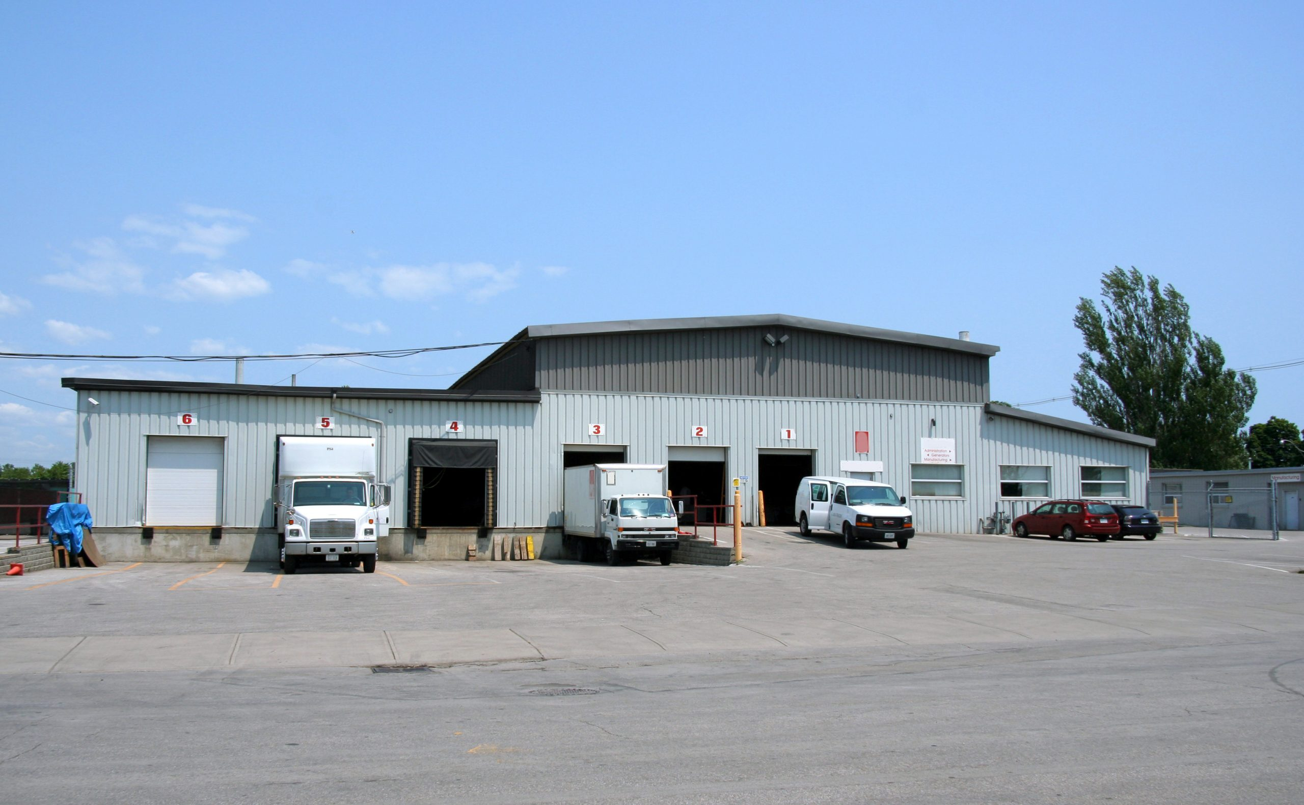 Small warehouse with trucks at loading docks.
