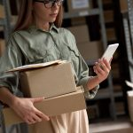 Female warehouse worker manager, small stock business owner holding phone and retail package