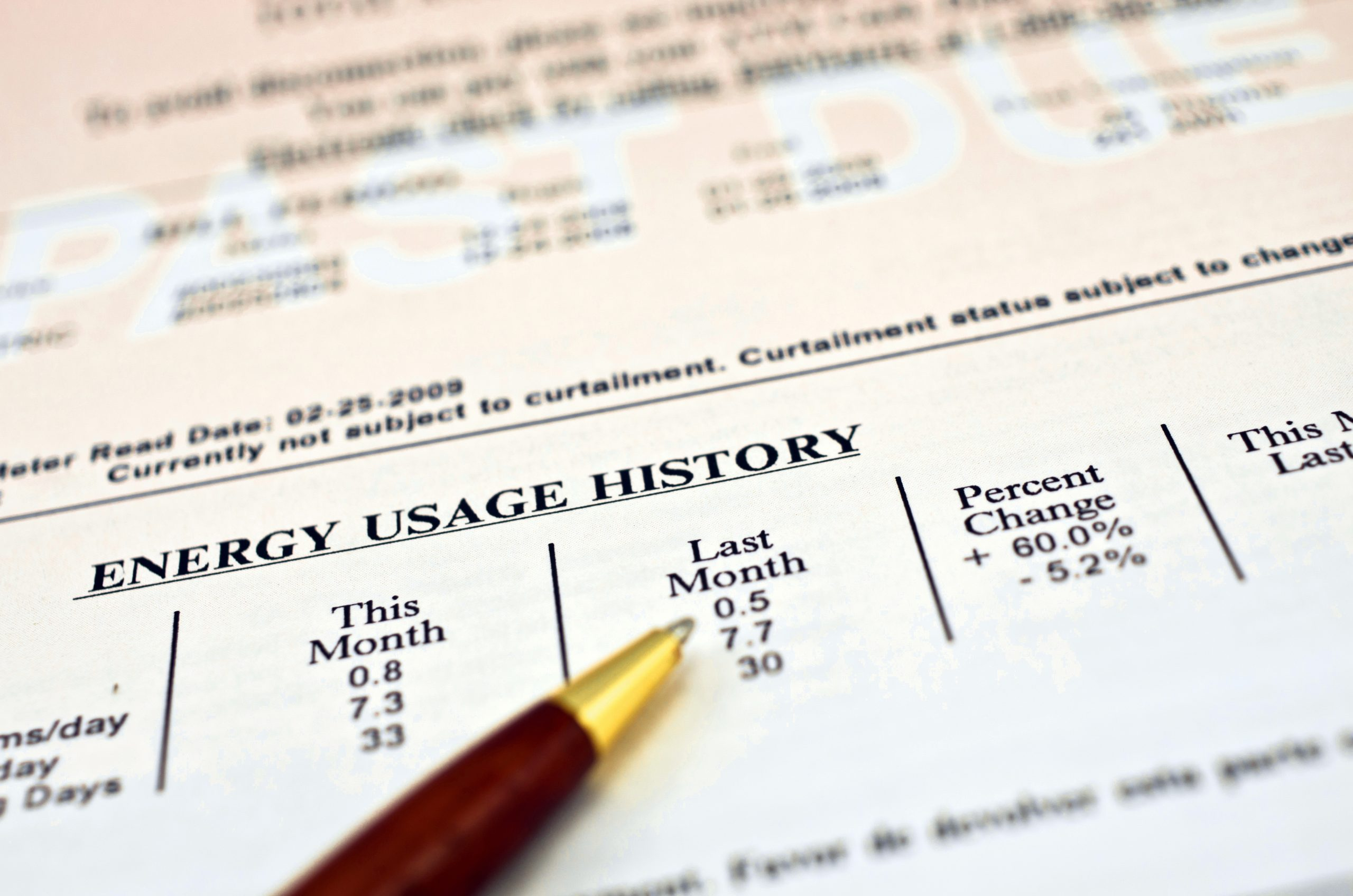 """Close up of a utility bill and ball pen showing a 60% energy usage increase over last month. In the background """"PAST DUE"""" can be read in big white letters on faded red background."""